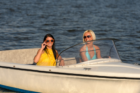 Young women in sunglasses sitting in motorboat driving photo