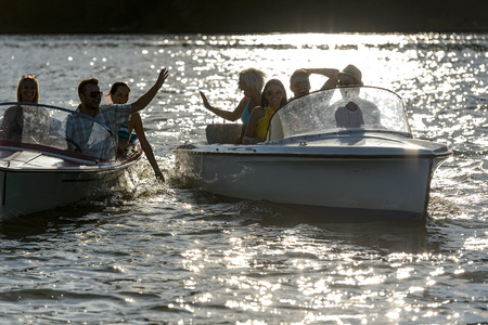Silhouette of young people enjoying summer motorboat on lake photo