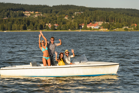 lipno: Young friends waving from speed boat in the sunshine
