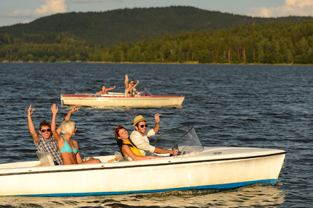motorboats: Group of cheerful friends racing with motorboats on river
