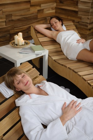 Two young women relaxing on wooden chair at luxury spa photo