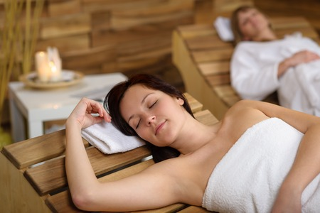 Happy young woman relaxing on wooden chair at luxury spa Stock Photo - 30414137