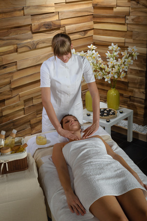 Young therapist massaging cleavage to attractive  woman at spa photo