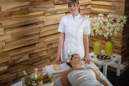 Female masseur give massage treatment in luxury health spa centre photo
