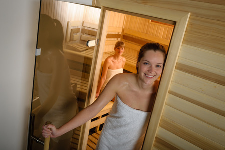 Sweaty young woman standing in front of the sauna photo