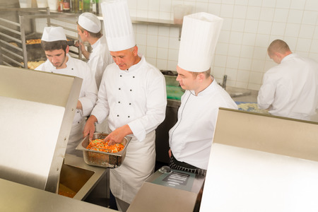 Professional chef cook with team prepare food in industrial kitchen photo