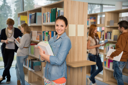 Smiling student holding books with friends talking in college library photo