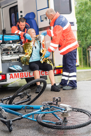 Emergency paramedics helping woman in ambulance bike accident thermal foil