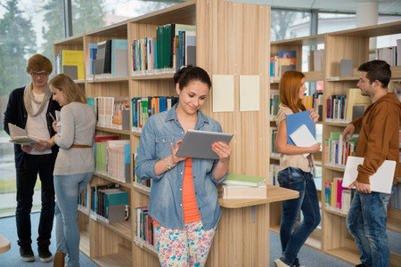 College student using tablet with classmates chatting in library photo