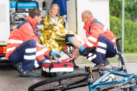 accidente laboral: Mujer en bicicleta Accidente Obtenga ayuda de emergencia param�dicos en una ambulancia Foto de archivo