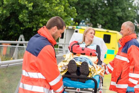 paciente en camilla: Paciente hablando con los paramédicos después de lesión del accidente ayuda brazo emergencia