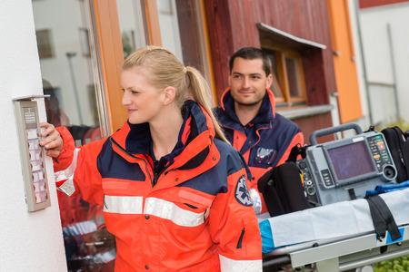 Les ambulanciers paramédicaux d'appel du logement visite ambulance aide femme de sonner l'aide de l'homme Banque d'images - 30414236