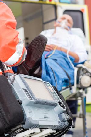 ambulance emergency: Emergency defibrillator patient with oxygen mask on ambulance stretcher