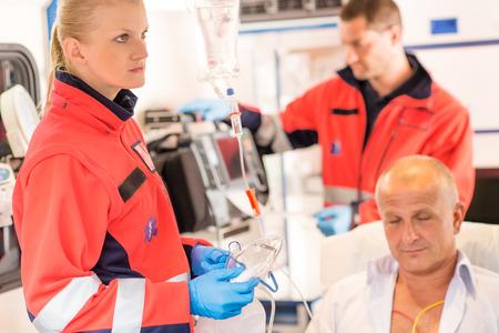 Paramedics in ambulance with patient heart attack treatment emergency sick Standard-Bild