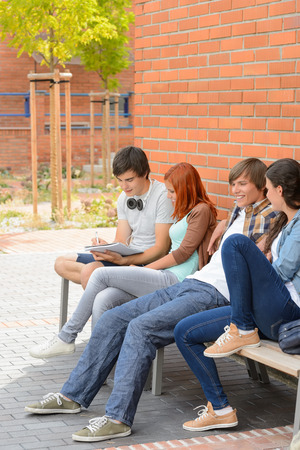 Group of students friends hanging out sitting outside college campus photo