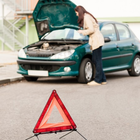 Woman trying to fix her broken car breakdown sign triangle Stock Photo - 30414323