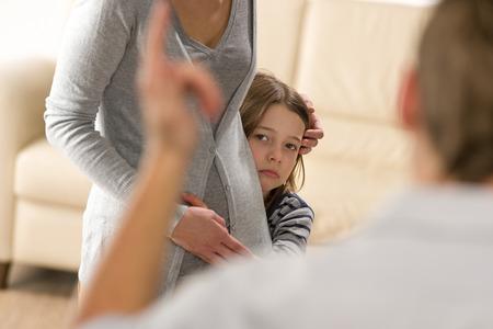 personas discutiendo: Niña asustada que oculta detrás de la madre del padre violento