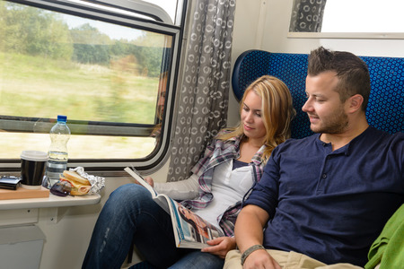 Couple traveling by train reading magazine smiling vacation passengers tourists photo