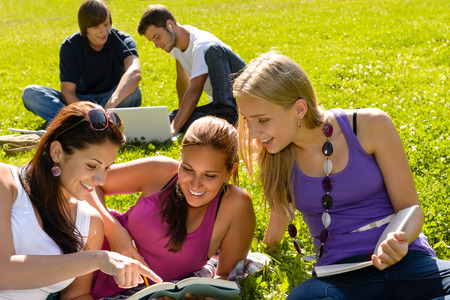 Teens studying in park reading book students happy campus research photo