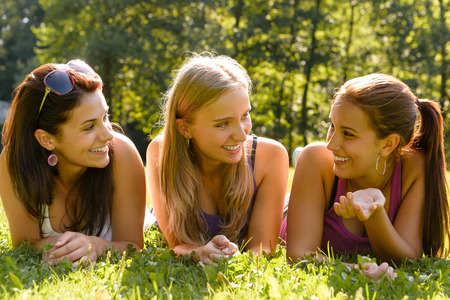 Teen women talking and relaxing in park happy grass friends photo