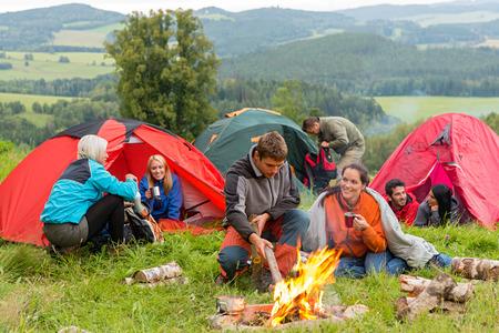 Groep jonge studenten doorbrengen weekend samen in tenten kampvuur Stockfoto