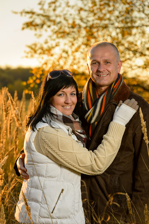 wedding portrait: Romantic couple hugging in autumn countryside backlit by sunset