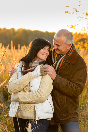 Couple in love hugging sunset autumn countryside looking each other