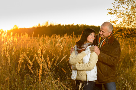 mid age: Romantic couple hugging during autumn sunset countryside looking at each other