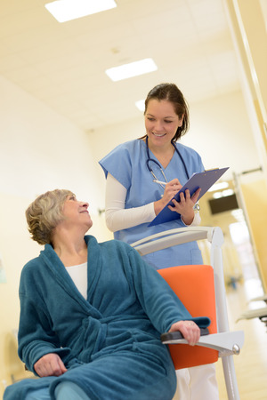disabled seniors: Smiling young female nurse watch senior patient in hospital while holding her files