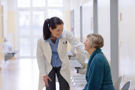 Lachend vrouwelijke arts in gesprek met senior patiënt in het ziekenhuis