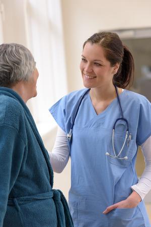 patient care: Smiling female doctor taking care of senior patient in hospital corridor