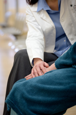 patient care: Doctor holding senior patient hands in hospital Stock Photo