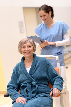 Senior patient in wheelchair smiling, nurse looking at her patient files