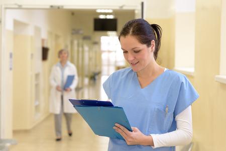 enfermera con paciente: Sonriente mujer joven enfermera en el hospital mirando hacia abajo a los archivos de pacientes