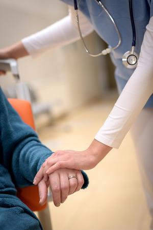 Close-up de l'infirmière tenant la main du patient âgé assis en fauteuil roulant