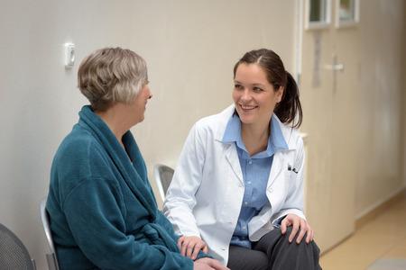 Sourire femme médecin parle d'patient plus âgé à l'hôpital Banque d'images