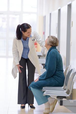 Glimlachende vrouwelijke arts glimlachend met senior patiënt in het ziekenhuis corridor Stockfoto
