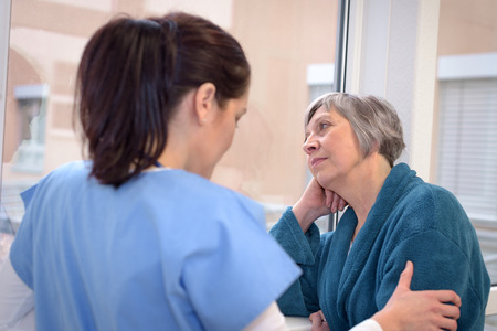 Sad senior patient in hospital corridor looking outside with young nurse Stock Photo