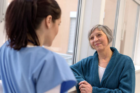 Smiling senior patient in hospital corridor looking at a young nurse