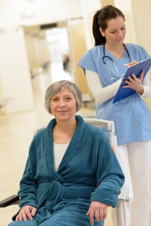 Patient plus âgé en fauteuil roulant dans le couloir de l'hôpital en face de l'infirmière en regardant ses dossiers patients Banque d'images