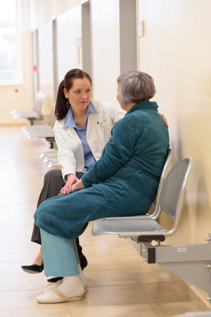 Femme médecin assis avec patient plus âgé dans le couloir de l'hôpital