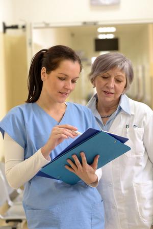 Femme médecin senior et jeune femme infirmière souriante regardant les dossiers des patients