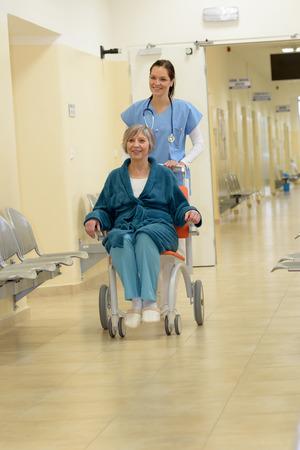 Sourire jeune infirmière à l'hôpital poussant patient plus âgé en fauteuil roulant dans le couloir de l'hôpital