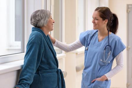 Smiling female nurse caring for senior patient in hospital corridor photo
