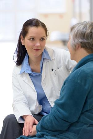 Female doctor comforting senior patient photo