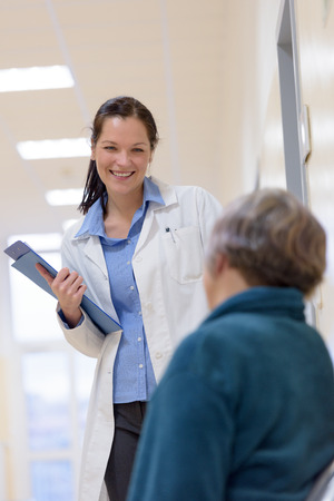 hospital patient: Female doctor smiling to senior patient in hospital Stock Photo