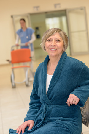 Smiling senior female patient waiting in  hospital for nurse with wheelchair photo