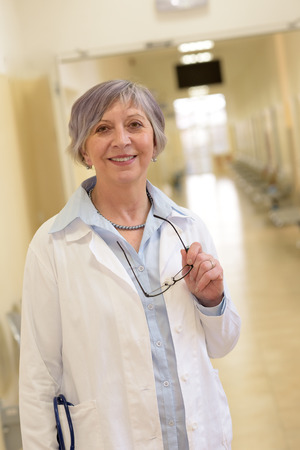 Senior doctor standing in hospital corridor smiling photo