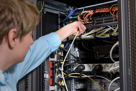 Datacenter specialist connects network cables to server patch panel
