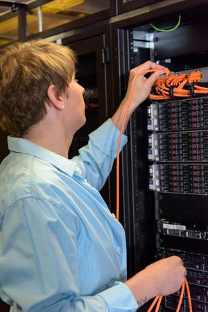 IT specialist controlling server in datacenter and rack of network harddisks